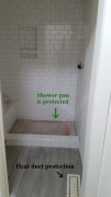 Tile being installed in boys' shower. Shower pan is protected