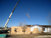 Roof trusses are being lifted into position by crane operator
