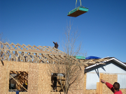 Roof sheathing is lifted by crane operator
