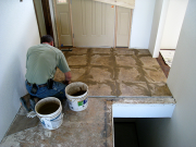 Don working on tile by entry