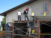 Stucco crew applies finish coat