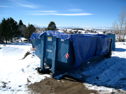 Dumpster is covered with tarp to keep trash from flying